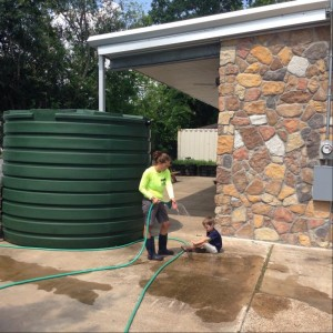 Sharon teaching my son how the rainwater is collected and held in the green basin and then used to water the plants.