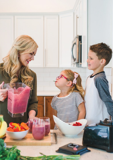 A photo of Natalie making a smoothie with her two kids